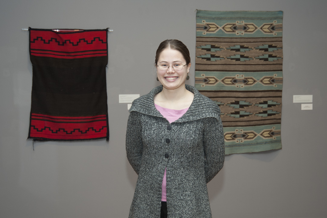 Kasey Kendall, an ND student who participated in Prof. Joanne Mack's 2011 class that curated an exhibition. She stands next to the display of Native American objects that she selected, researched and described in exhibition text panels and labels.