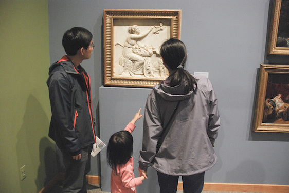 A family looking at art in the 19th Century Gallery