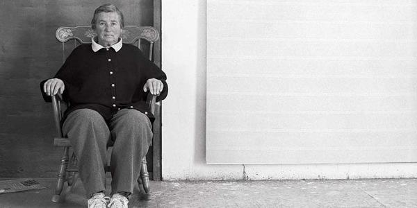 Artist Agnes Martin sitting in rocker in front of one of her paintings.